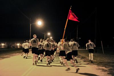 Soldiers take turns running around the formation with the guideon during a weekly battery runs at Fort Hood, Texas.